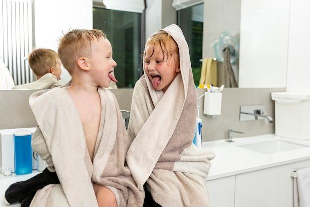 Mittlere schusskinder, die im badezimmer sitzen