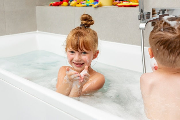 Mittlere schusskinder, die in der badewanne sitzen