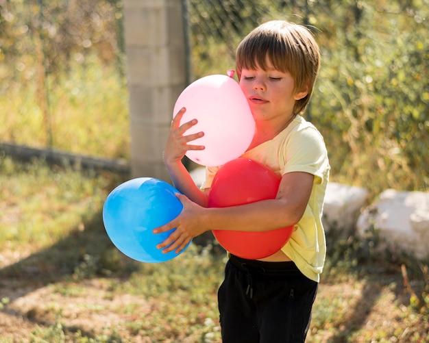 Mittlere schusskinder, die luftballons halten