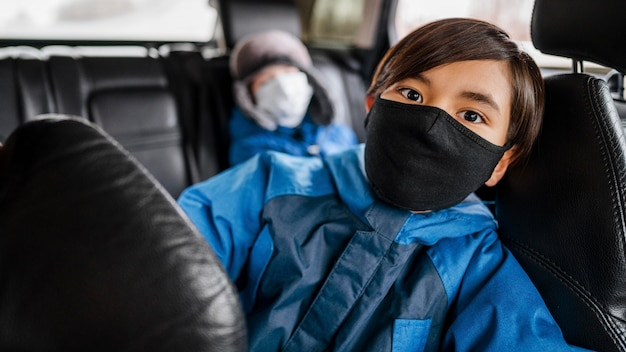 Mittlere schusskinder, die masken im auto tragen