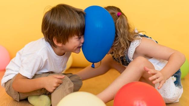 Mittlere schusskinder, die mit ballon spielen