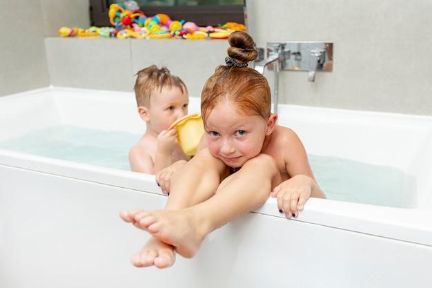 Mittlere schusskleinkinder in der badewanne