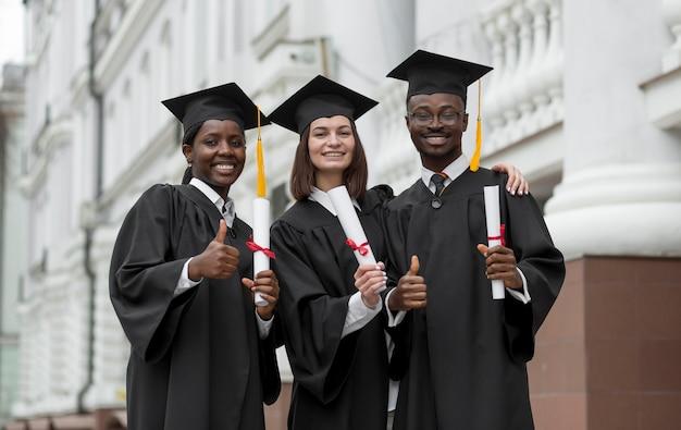 Mittlere schusskollegen posieren mit diplomen