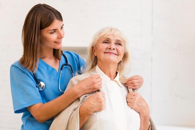 Mittlere schusskrankenschwester, die alter frau mit ihrem mantel hilft