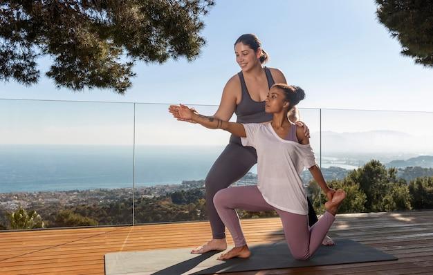 Mittlere schusslehrerin, die frau beim yoga hilft