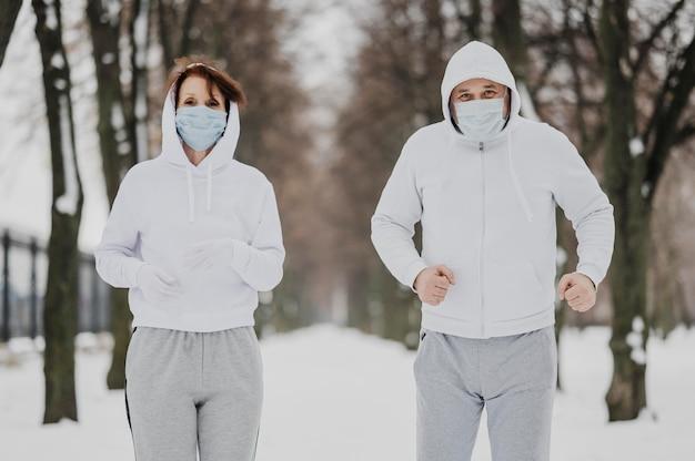 Mittlere schussleute, die mit masken laufen