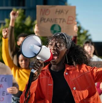 Mittlere schussleute, die mit megaphon protestieren