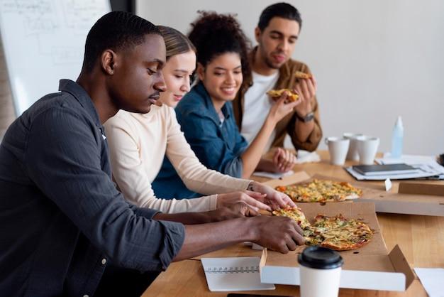 Mittlere schussleute, die pizza bei der arbeit essen