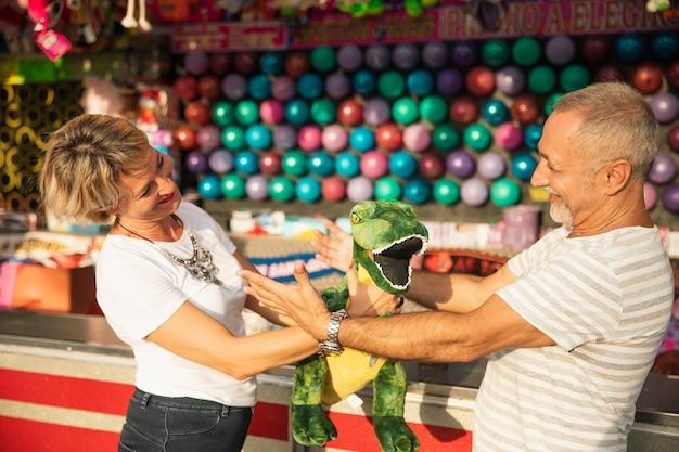 Mittlere schussleute mit dinosaurier am freizeitpark