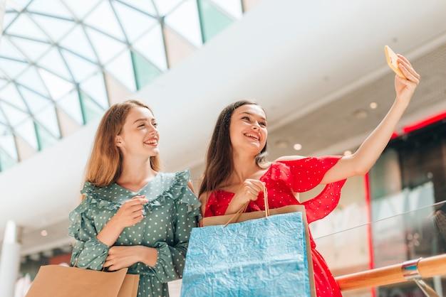 Mittlere schussmädchen am mall, das ein selfie nimmt