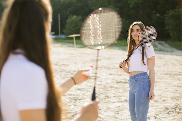 Mittlere schussmädchen, die badminton spielen