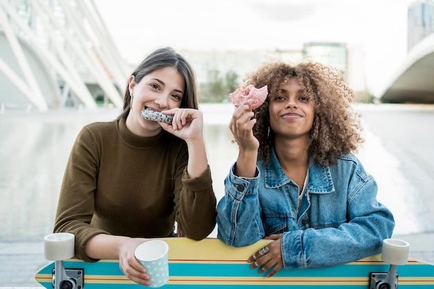 Mittlere schussmädchen, die donuts essen