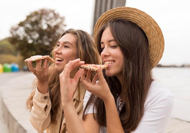 Mittlere schussmädchen, die pizza essen
