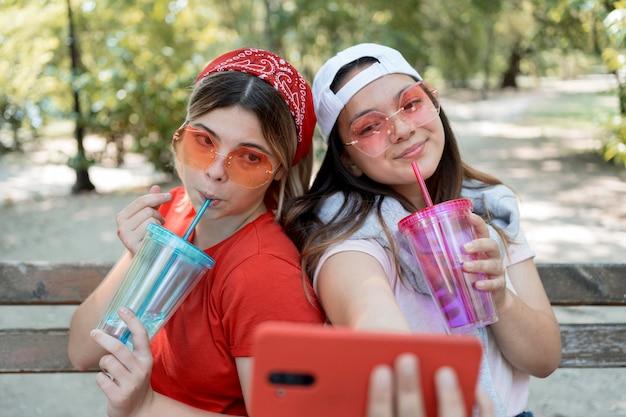 Mittlere schussmädchen, die selfie mit getränken nehmen