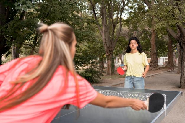 Mittlere schussmädchen, die tischtennis spielen