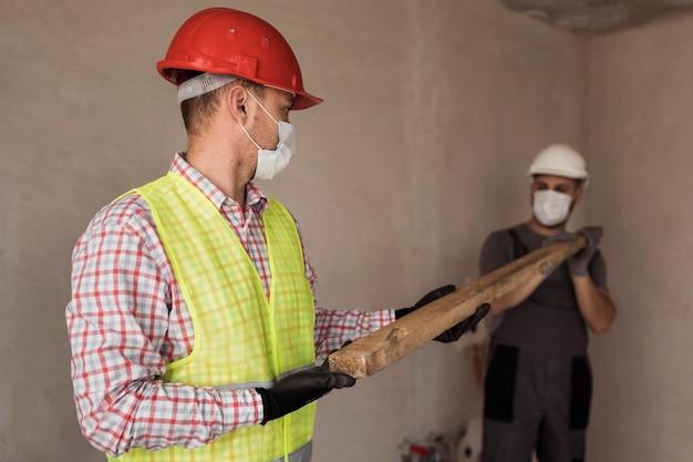 Mittlere schussmänner, die mit medizinischen masken arbeiten