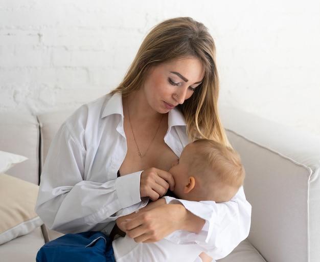 Mittlere schussmutter, die ihr baby stillt