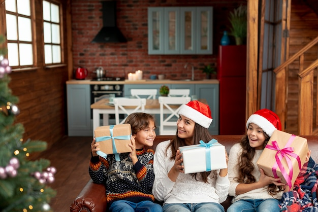 Mittlere schussmutter und -kinder mit geschenken