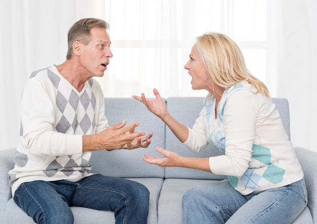 Mittlere schusspaare, die auf der couch argumentieren