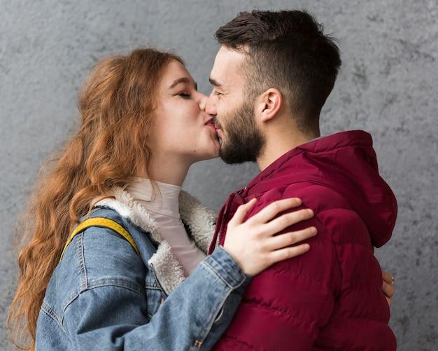 Mittlere schusspaare, die draußen küssen