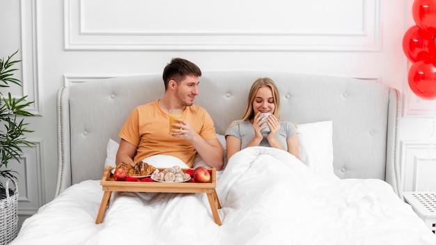 Mittlere schusspaare, die im schlafzimmer frühstücken