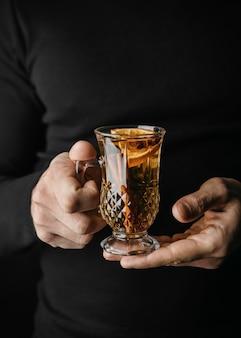 Mittlere schussperson, die glas mit wintergetränk hält