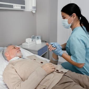 Mittlere schussschwester, die die hand des patienten hält
