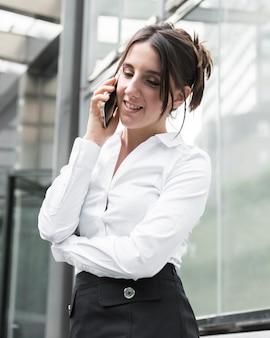 Mittlere schusssmileyfrau, die telefonisch spricht