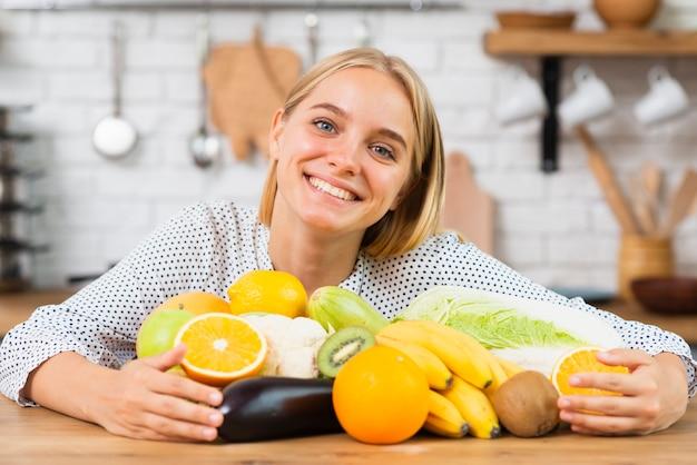 Mittlere schusssmileyfrau mit köstlichen früchten