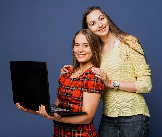 Mittlere schusssmileymädchen, die mit laptop aufwerfen