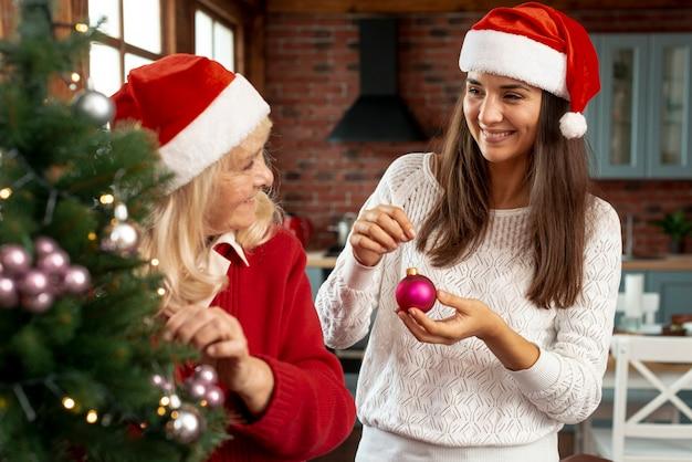 Mittlere schusssmileymutter und -tochter, die den weihnachtsbaum verzieren