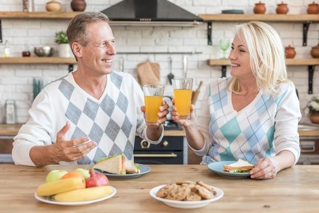 Mittlere schusssmileypaare in der küche, die einen toast hat
