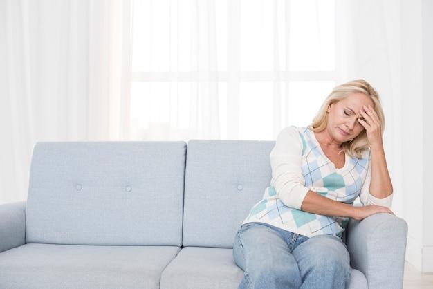 Mittlere schussumkippenfrau, die auf der couch sitzt
