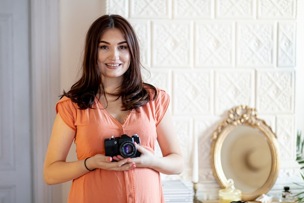 Mittlere schwangere frau des schusses, die eine kamera hält