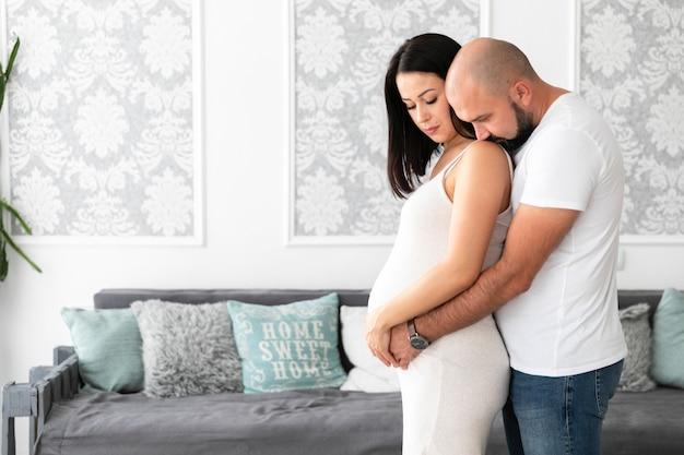Mittlere schwangere frau des schusses, die zeit mit ihrem ehemann verbringt