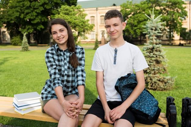 Mittlere seitenansicht von teenagern, die auf einer bank sitzen