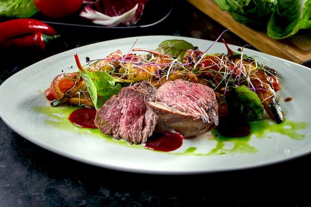Mittlere seltene rindfleischmedaillons mit gemüsegarnitur, serviert auf einem weißen teller. dunkler marmortisch. grillfleisch, restaurantessen. leckeres steak
