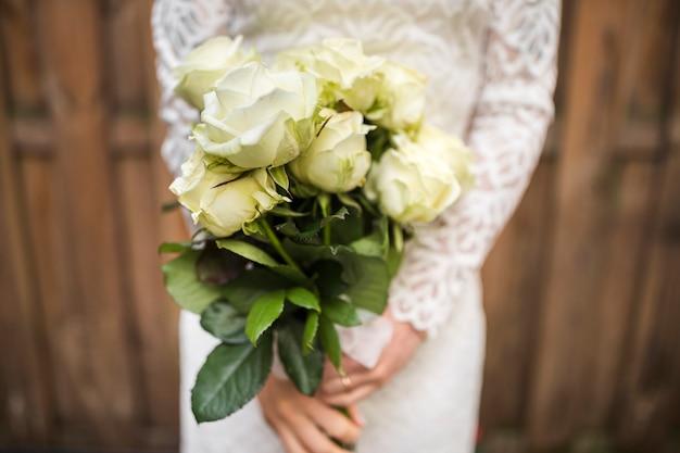 Mittlerer abschnitt der braut schönen rosenblumenstrauß halten