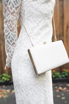 Mittlerer abschnitt der frau im weißen kleid mit kupplung