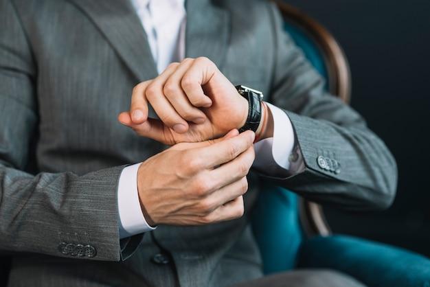 Mittlerer abschnitt der hand eines geschäftsmannes, welche die zeit auf armbanduhr aufpasst
