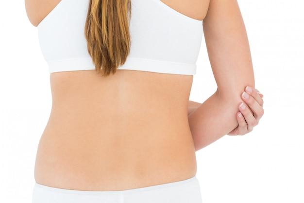 Mittlerer abschnitt der hinteren ansicht einer sitzfrau mit ellbogenschmerz