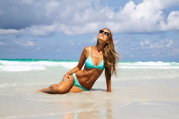 Mittlerer abschnitt der jungen frau im blauen bikini ein sonnenbad nehmend auf weißem sand. mode mädchen am tropischen strand bräunen