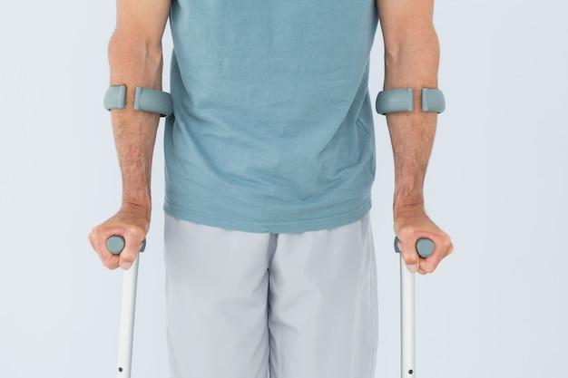 Mittlerer abschnitt der nahaufnahme eines mannes mit krücken