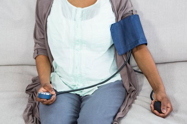 Mittlerer abschnitt der schwangeren frau blutdruck im wohnzimmer zu hause überprüfend