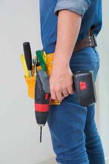 Mittlerer abschnitt der seitenansicht eines heimwerkers mit bohrgerät und toolbelt