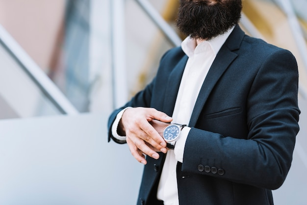 Mittlerer abschnitt des geschäftsmannes armbanduhr auf seiner hand halten