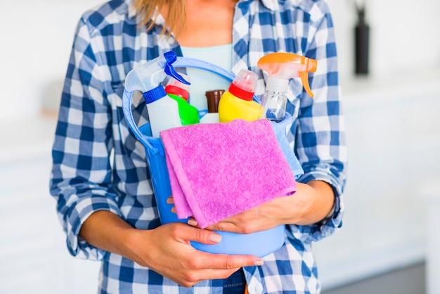 Mittlerer abschnitt des hausmeisters reinigungsausrüstungen im blauen eimer halten