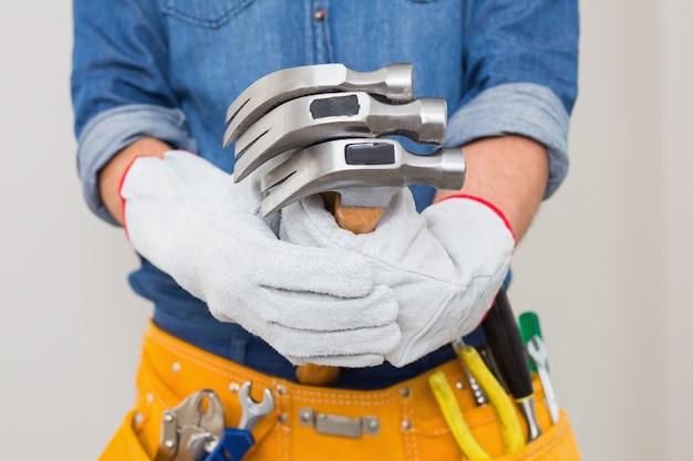 Mittlerer abschnitt des heimwerkers hammer mit werkzeuggurt um taille halten