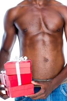 Mittlerer abschnitt des hemdlosen machomannes, der geschenke hält