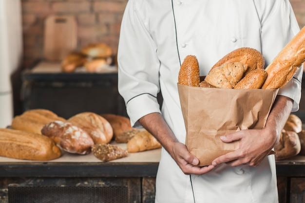 Mittlerer abschnitt des männlichen bäckers papiertüte mit broten halten